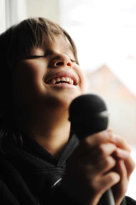 Kind am Mikrofon beim Ausführen einer Übung fürs Stimmtraining