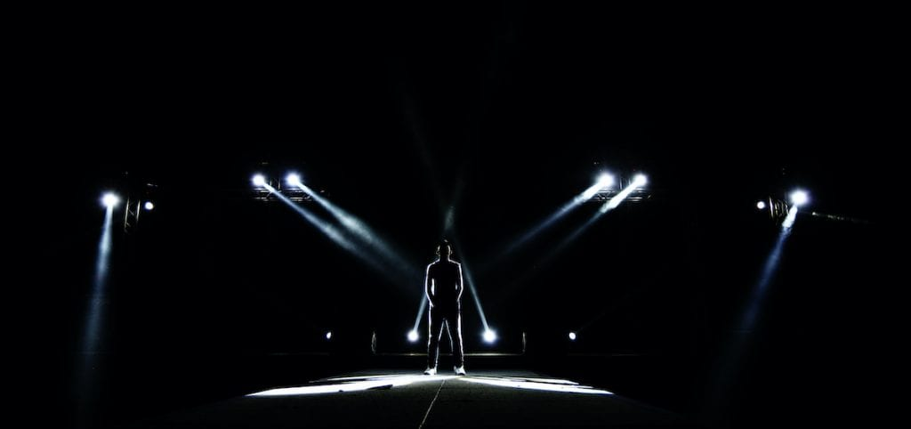 Men standing in the light on a stage