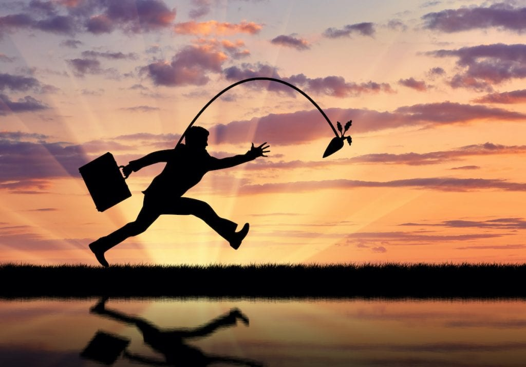 Silhouette of businessman running for the carrot and reflection in water.